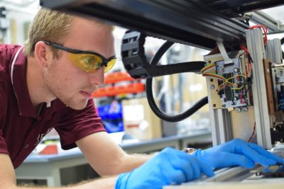 A student wearing yellow safety glasses and a maroon polo works in the DREAM machine.